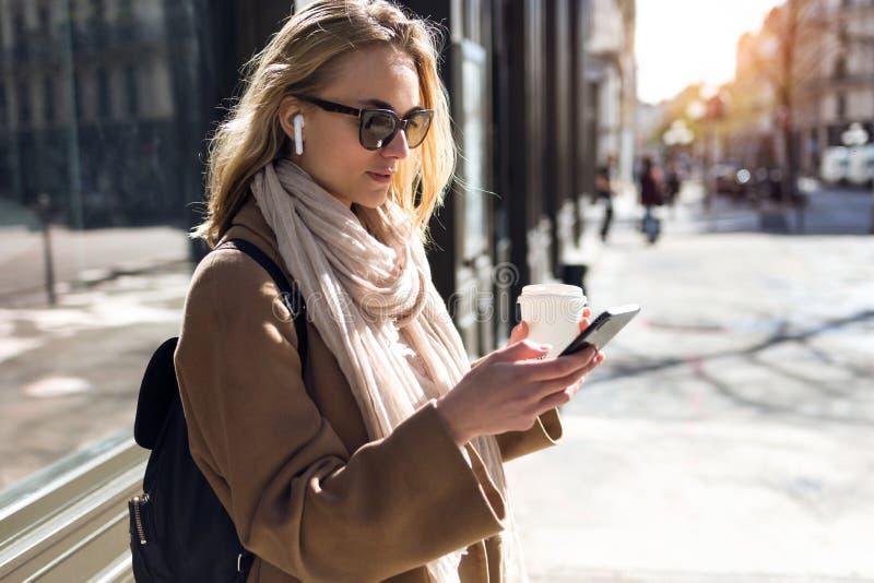Mujer joven bonita que escucha la m?sica con los auriculares inal?mbricos y el smartphone en la calle imágenes de archivo libres de regalías