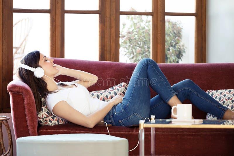 Mujer joven bonita que escucha la música mientras que se relaja en el sofá en casa foto de archivo