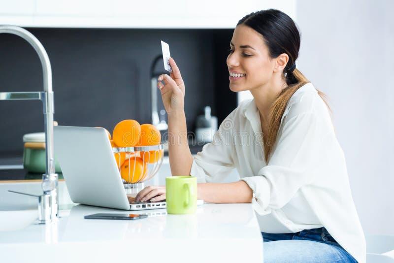 Mujer joven bonita que hace compras en línea con la tarjeta de crédito mientras que permanece en la cocina en casa fotos de archivo