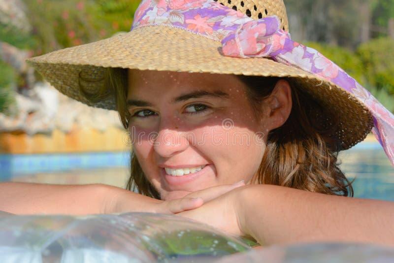 Mujer joven bonita que lleva un sombrero, sonriendo y feliz, al aire libre fotografía de archivo