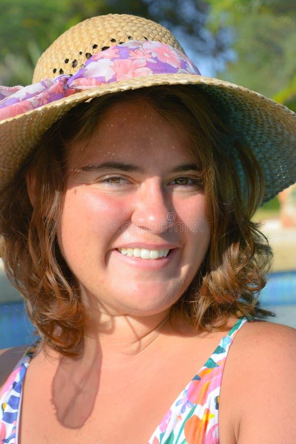 Mujer joven bonita que lleva un sombrero, sonriendo y feliz, al aire libre fotografía de archivo libre de regalías