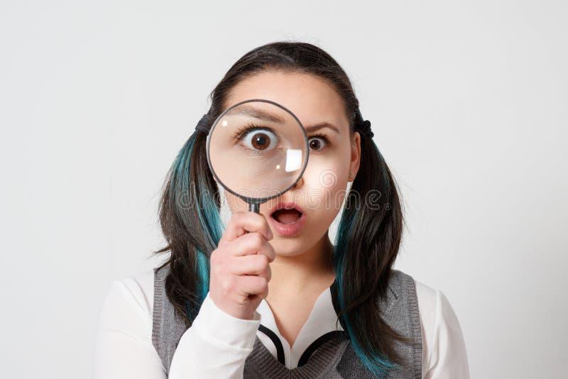 Mujer joven bonita que mira con magnificar imagenes de archivo
