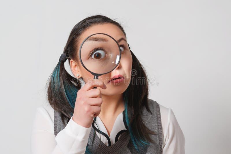 Mujer joven bonita que mira con magnificar imagen de archivo