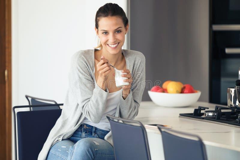 Mujer joven bonita que mira la cámara mientras que come el yogur en la cocina en casa fotos de archivo libres de regalías