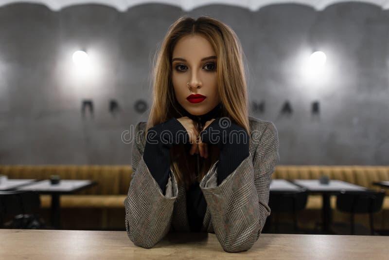 Mujer joven bonita que sorprende con maquillaje hermoso con los labios rojos con una nariz perforada en una chaqueta a cuadros de fotos de archivo