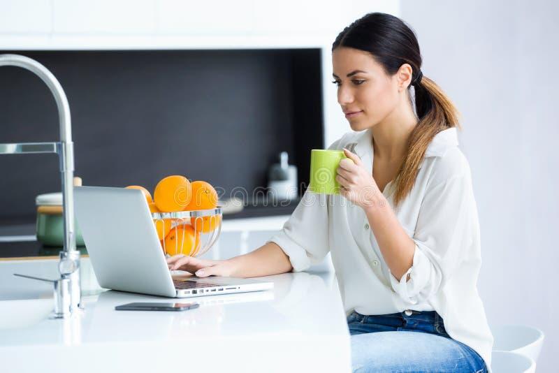 Mujer joven bonita usando su ordenador portátil mientras que taza de consumición de café en la cocina en casa imagen de archivo libre de regalías