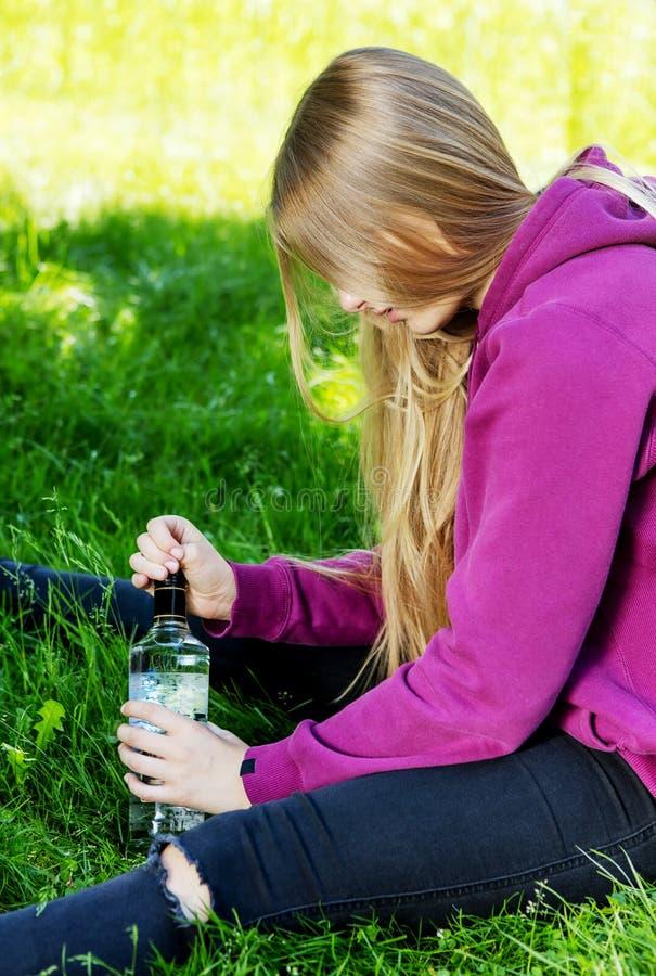Mujer joven borracha con la botella de alcohol fotos de archivo libres de regalías