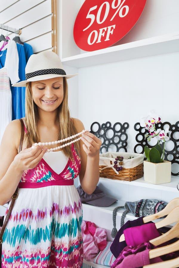 Mujer joven brillante que elige un collar fotos de archivo libres de regalías