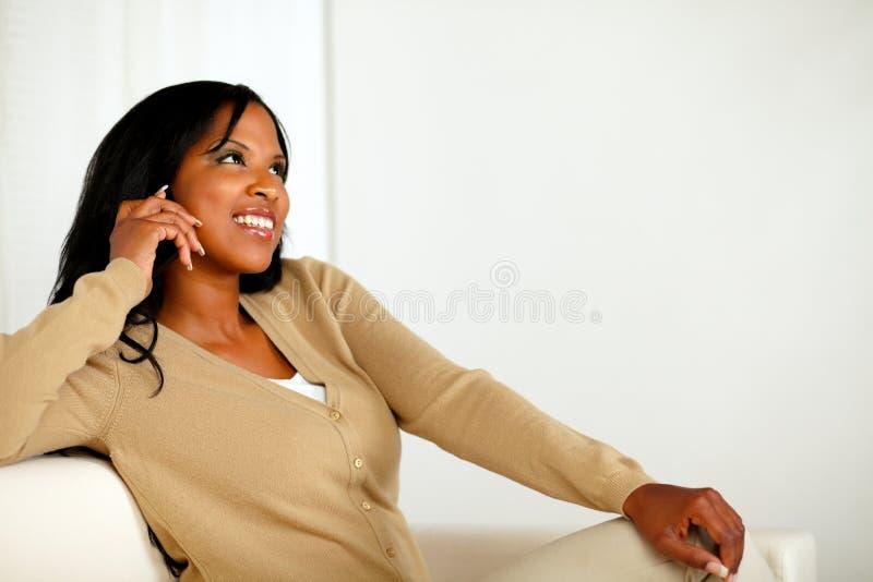 Mujer joven cómoda que mira para arriba con el teléfono celular imagen de archivo