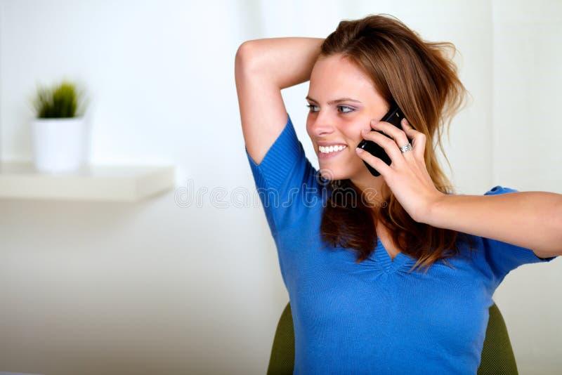Mujer joven cómoda rubia que conversa en el teléfono fotografía de archivo libre de regalías
