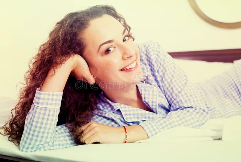 Mujer joven cabelluda rizada que se relaja en cama imagen de archivo libre de regalías