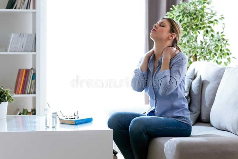Mujer joven cansada con el dolor de cuello que se sienta en el sofá en casa imagenes de archivo