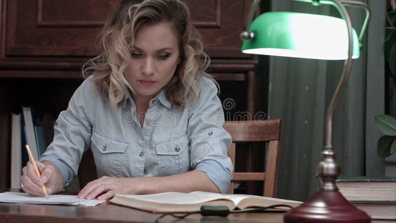 Mujer joven cansada que acaba su informe, cerrando el libro, apagando la lámpara y dejando su escritorio foto de archivo
