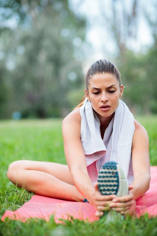 Mujer joven cansada que estira después de un entrenamiento en un parque imagen de archivo