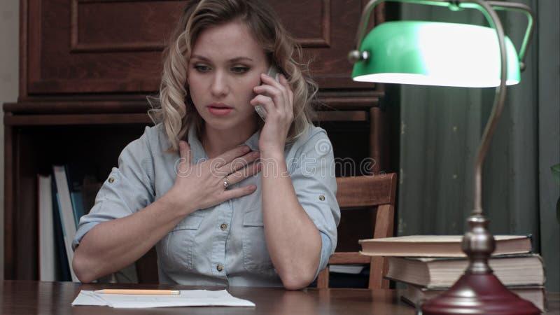 Mujer joven cansada que se sienta en su escritorio receiveing noticias muy malas en el teléfono imagen de archivo