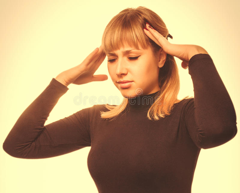 Mujer joven cansada retrato en el dolor de cabeza del dolor y de la tensión, sosteniéndose fotos de archivo