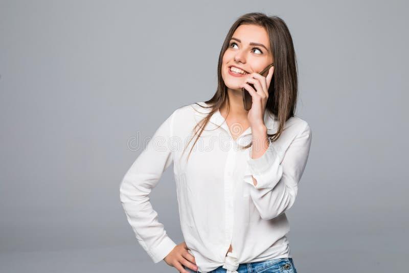 Mujer joven casual atractiva hermosa que habla en su teléfono móvil Estudio tirado sobre fondo gris fotos de archivo libres de regalías