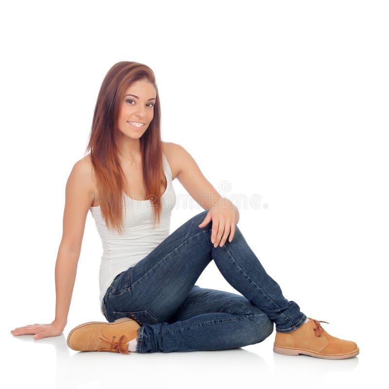 Mujer joven casual que se sienta en el piso fotografía de archivo libre de regalías