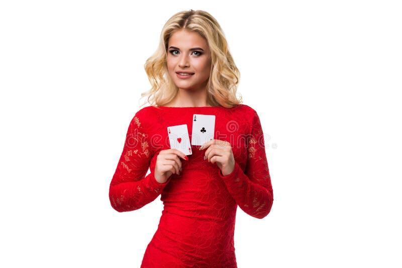 Mujer joven caucásica con el pelo rubio ligero largo en el equipo de la tarde que sostiene naipes Aislado póker imágenes de archivo libres de regalías