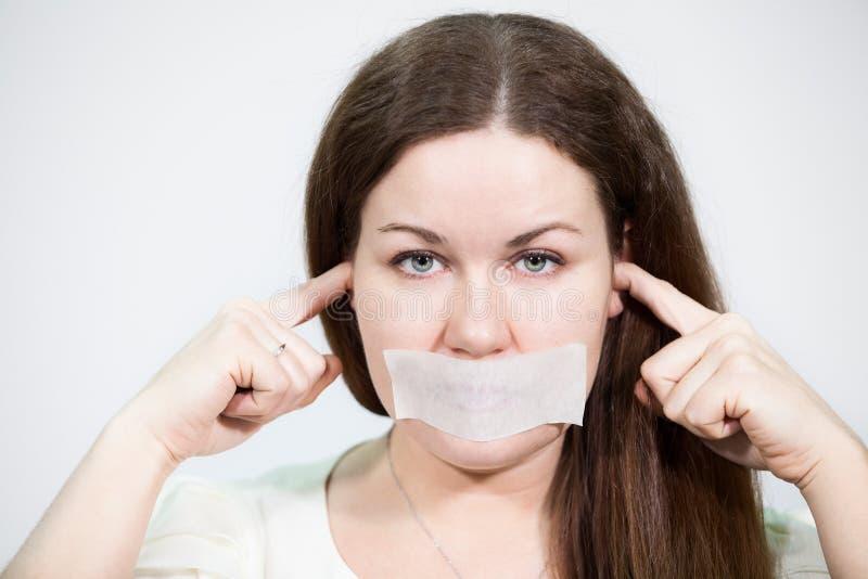 Mujer joven caucásica con la cinta pegada en su boca y oídos cerrados, fondo gris imagen de archivo