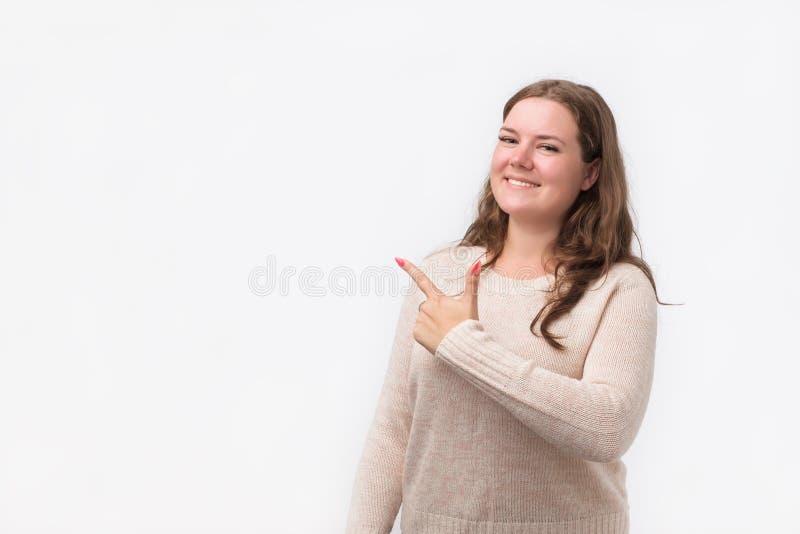 Mujer joven caucásica feliz en suéter que sonríe ampliamente en la cámara, señalando los fingeres lejos, mostrando algo interesan fotografía de archivo