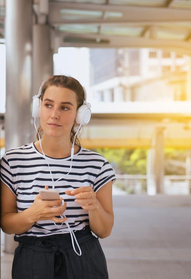 Mujer joven caucásica hermosa usando el auricular y el escuchar la música al aire libre, buena actitud, pensamiento positivo imagen de archivo libre de regalías