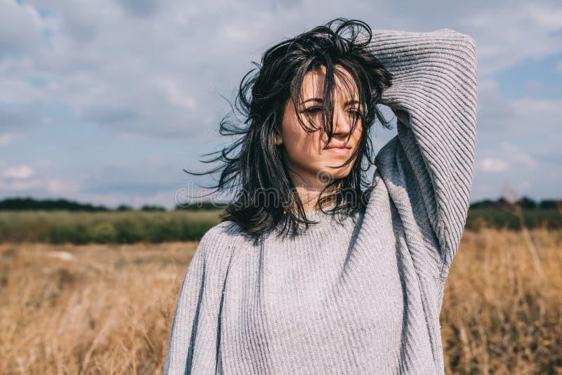 Mujer joven caucásica morena con el exterior ventoso del pelo que sopla, contra prado y el cielo Retrato de la hembra ideal que m imágenes de archivo libres de regalías