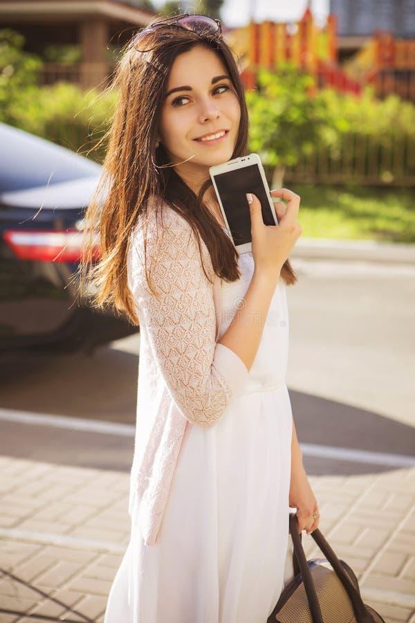 Mujer joven caucásica morena hermosa que se coloca cerca del coche negro imagen de archivo libre de regalías