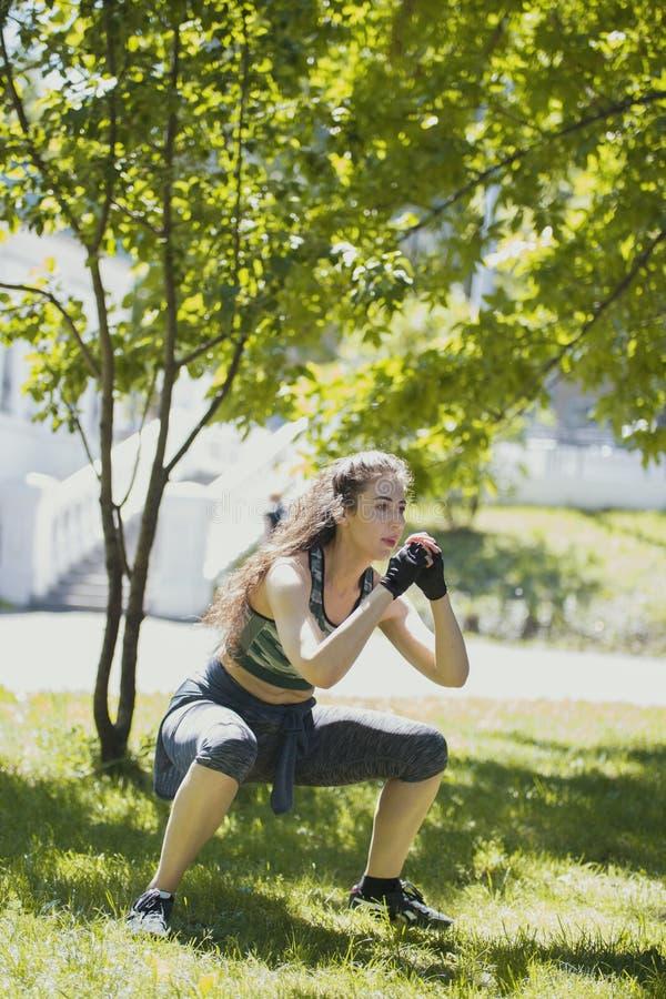 Mujer joven caucásica que hace sentar-UPS que ejercita en el parque en el día soleado foto de archivo