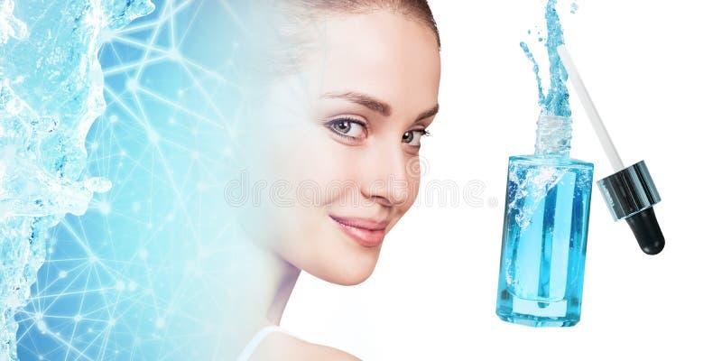 Mujer joven cerca de la botella cosmética azul debajo del chapoteo del agua azul imágenes de archivo libres de regalías