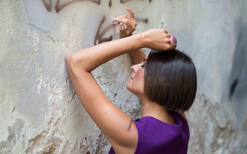Mujer joven cerca de la pared vieja pfoto foto de archivo