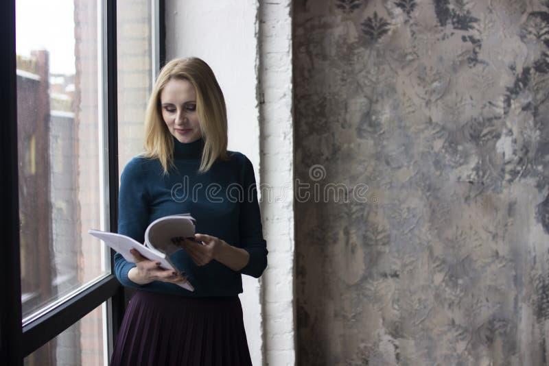 Mujer joven cerca de la ventana imágenes de archivo libres de regalías