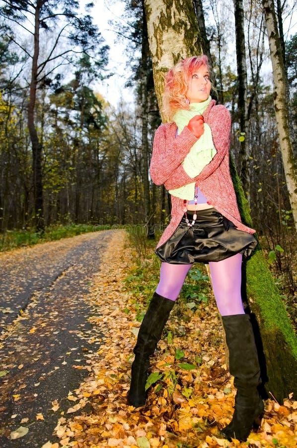 Mujer joven cerca del árbol imagenes de archivo