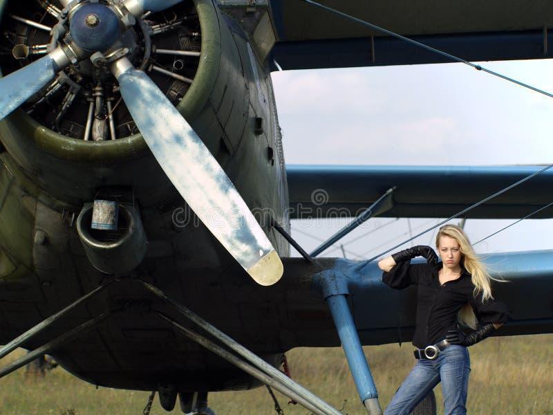 Mujer joven cerca del aeroplano de la vendimia imagenes de archivo