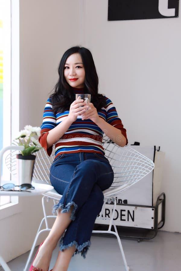Mujer joven china asiática hermosa que se relaja en una silla foto de archivo libre de regalías