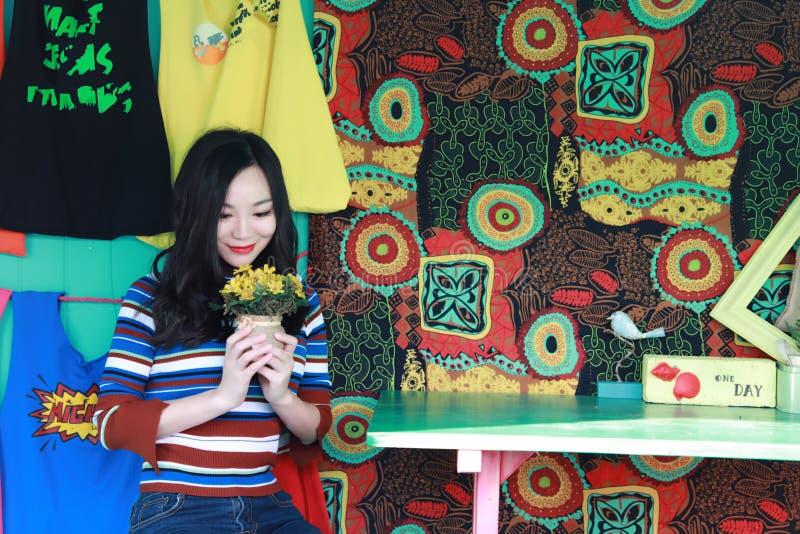 Mujer joven china asiática hermosa que se relaja en una silla fotografía de archivo libre de regalías