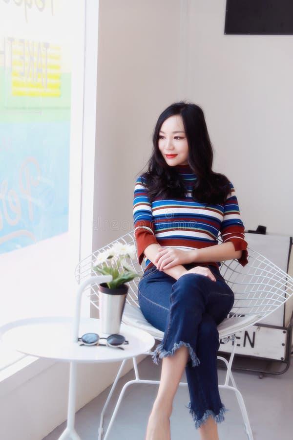 Mujer joven china asiática hermosa que se relaja en una silla imágenes de archivo libres de regalías