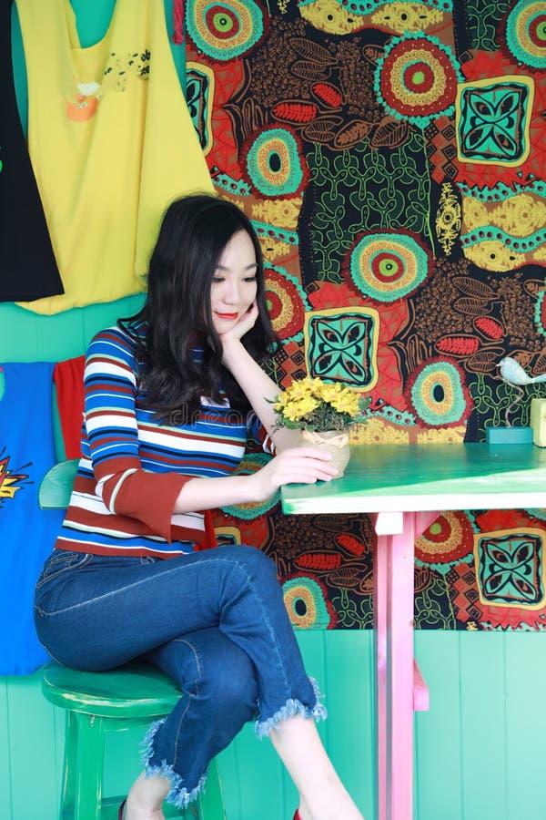 Mujer joven china asiática hermosa que se relaja en una silla fotos de archivo