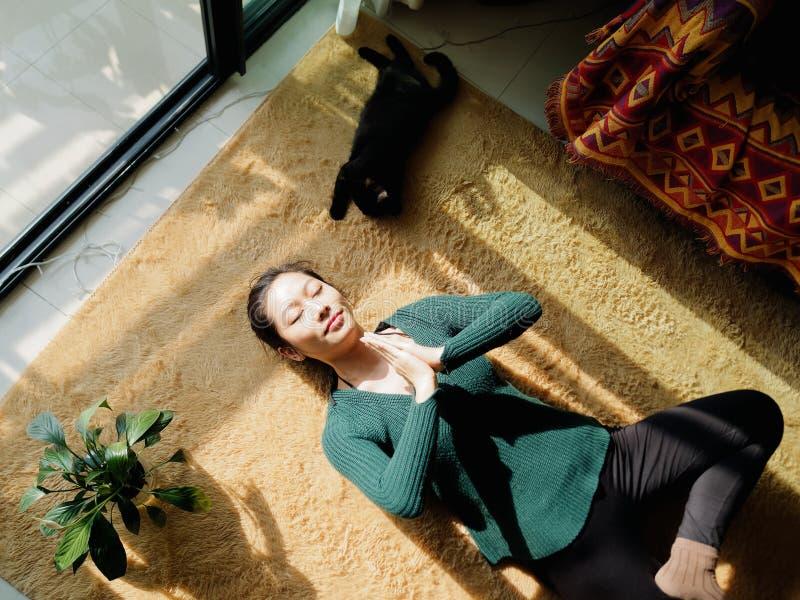 Mujer joven china bonita que medita en casa, mintiendo en piso con su gato negro en luz del sol imagen de archivo