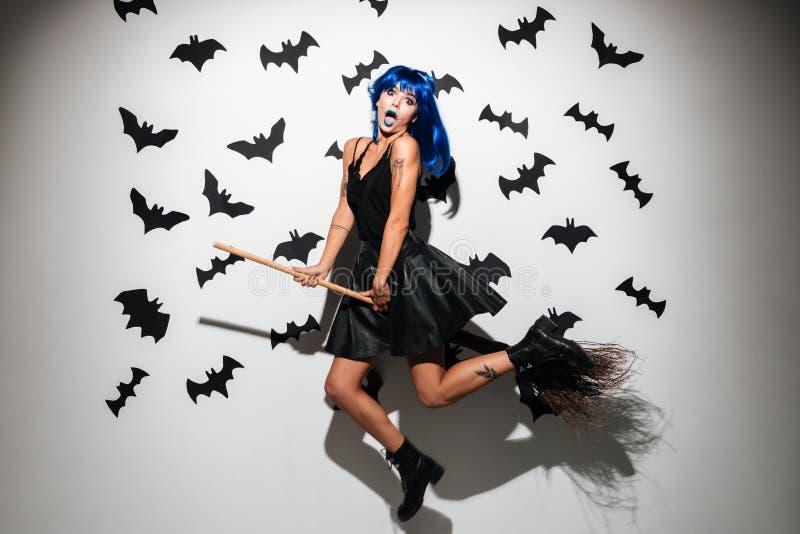 Mujer joven chocada emocional en el traje de Halloween de la bruja imagen de archivo