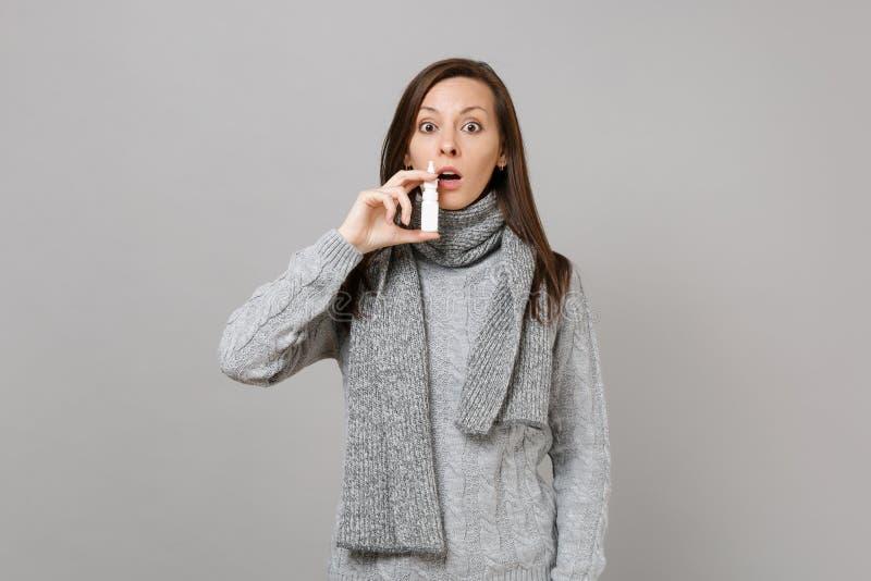 Mujer joven chocada en el suéter gris, tenencia de la bufanda usando descensos nasales aislada en fondo gris de la pared en estud imagen de archivo