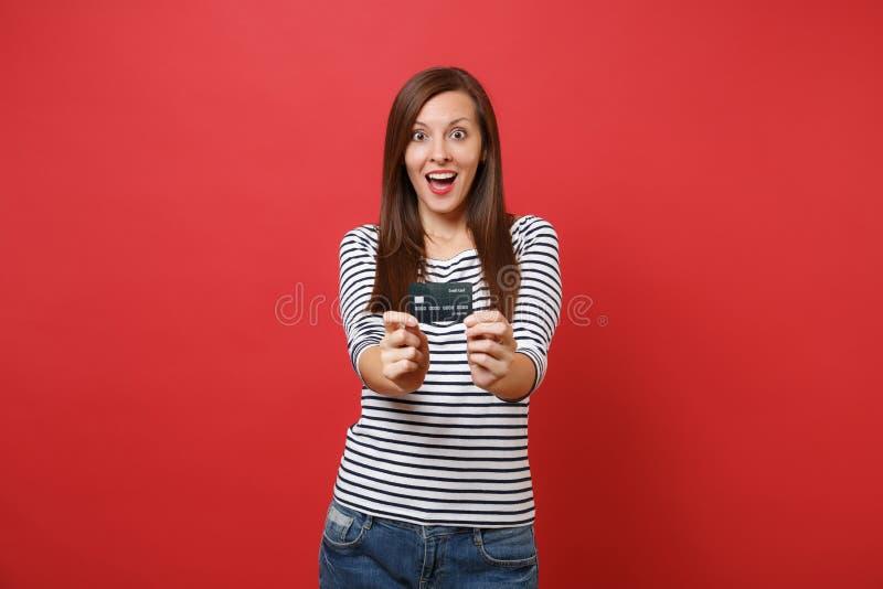 Mujer joven chocada en la ropa rayada que mantiene la boca abierta de par en par, pareciendo sorprendido, sosteniendo la tarjeta  fotos de archivo