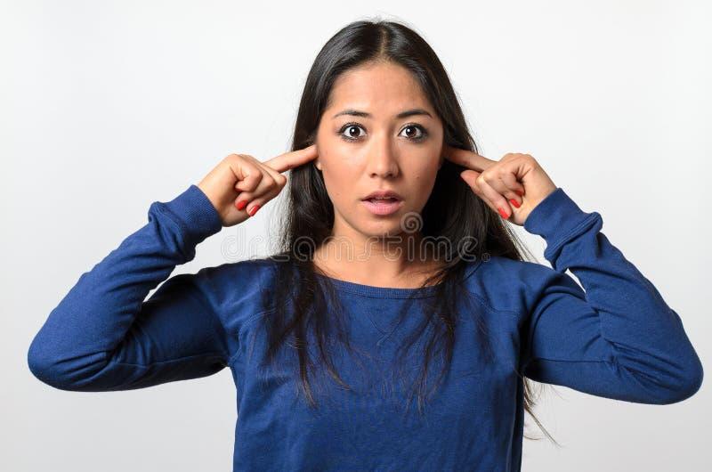 Mujer joven chocada que bloquea sus oídos fotografía de archivo
