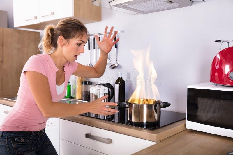 Mujer joven chocada que mira de cocinar el pote en el fuego foto de archivo