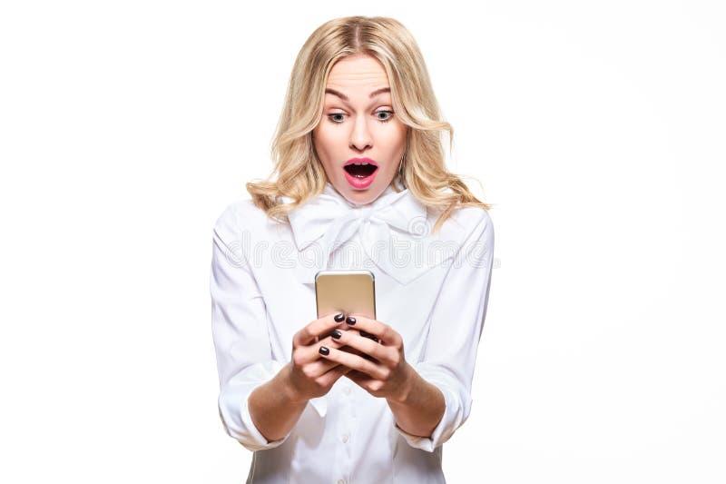 Mujer joven chocada que mira su teléfono móvil, gritando con incredulidad Mujer que mira fijamente el mensaje de texto impactante imagen de archivo libre de regalías