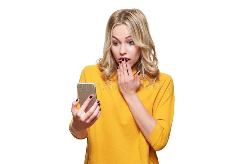 Mujer joven chocada que soporta su teléfono móvil, leyendo noticias impactantes Mujer con incredulidad, aislado sobre el fondo bl fotografía de archivo libre de regalías