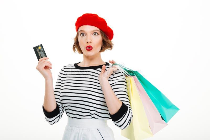 Mujer joven chocada que sostiene la tarjeta y los panieres de crédito foto de archivo libre de regalías