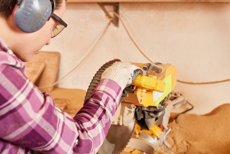 Mujer joven como aprendiz del carpintero mientras que asierra fotografía de archivo