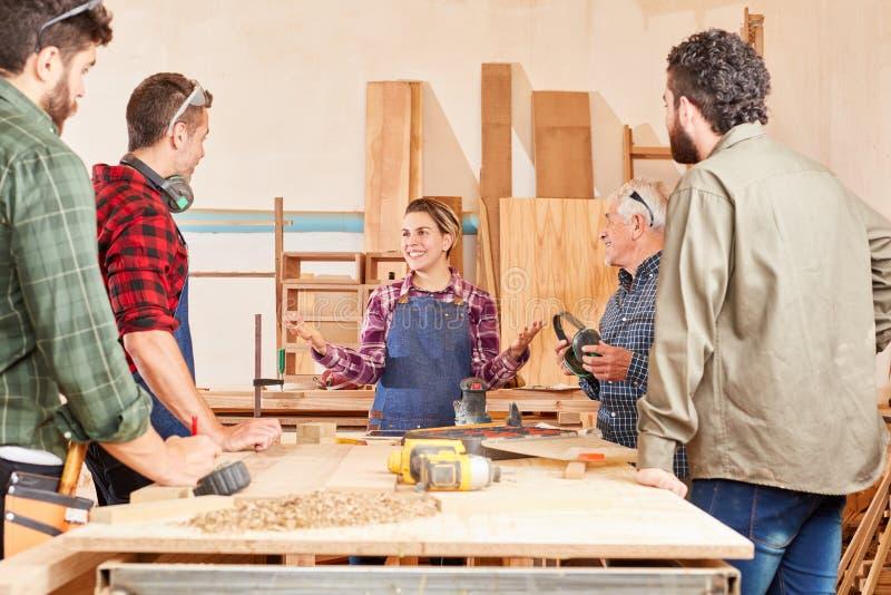 Mujer joven como aprendiz en la carpintería foto de archivo