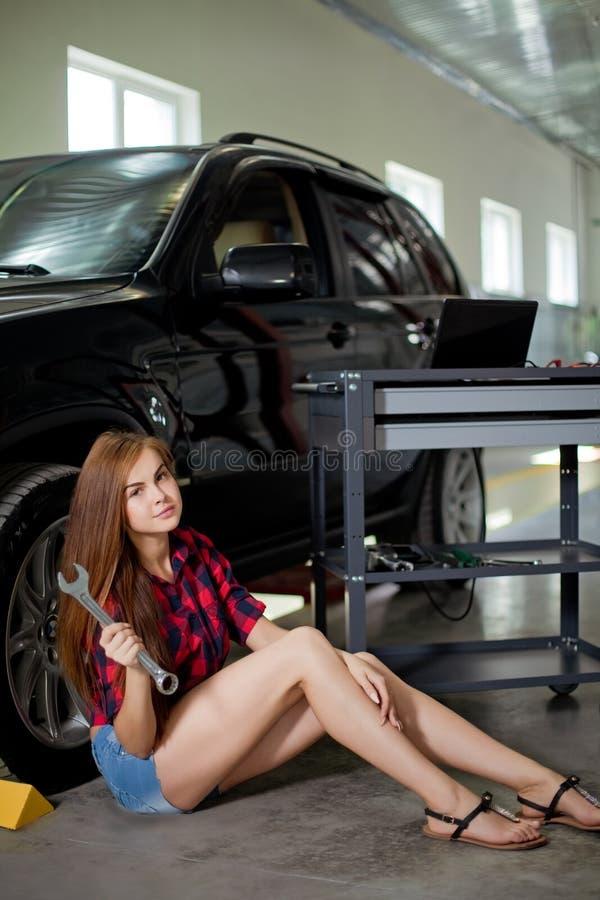 Mujer joven como mecánico en llave comprobada de la bruja de la camisa en garaje fotografía de archivo